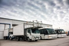 Aircraft caterers and airport buses in the parking lot. Near the garages Royalty Free Stock Photos