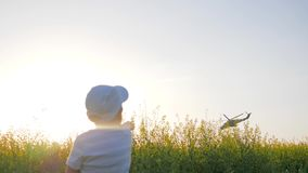 Aircraft in clear sky over field flowers, little boy into grass showing hand on flying helicopter, child sits into stock video footage