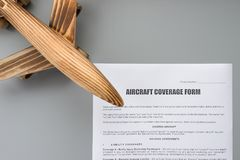 Aircraft coverage form and an airplane model close up. Concept of travel insurance Stock Photo