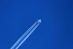 Aircraft in deep-blue sky with trail Royalty Free Stock Photography