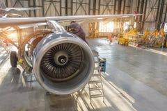 Aircraft engine repair, mechanic installs reverse hoods.  stock photography