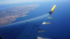 Aircraft flap of an airplane. Flying over an island Royalty Free Stock Image