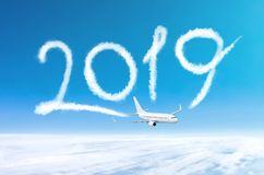 Aircraft flies leaving a trail 2019 of clouds in the sky. Happy New year concept travel.  royalty free stock image