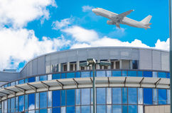 Aircraft flies over office building. Royalty Free Stock Photography