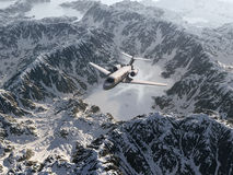 Aircraft flies over a snowy mountains Stock Image
