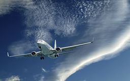 Aircraft in flight with CLOUD TYPE cloud in blue sky. Australi. An artistic skyscape view of a commercial passenger jet aircraft flying closeup in a vibrant blue stock photo
