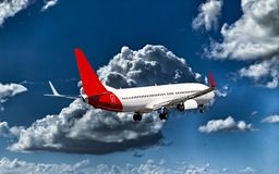 Aircraft in flight with cumulonimbus cloud in blue sky. Queensland. A passenger jet aircraft flyng in a vibrant blue sky, with well developed bright white royalty free stock image