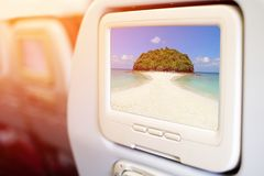 Aircraft In flight entertainment seat-back TV screens. Showing a picture of beautiful beach Royalty Free Stock Images