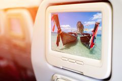 Aircraft In flight entertainment seat-back TV screens. Showing a picture of long tail boat and beautiful beach at Po-da Island, Andaman Sea, Krabi, South of Stock Photo