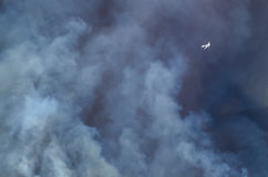 Aircraft Flying Ahead of the Dense White Smoke Rising from the Raging Wildfire Royalty Free Stock Photography