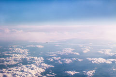 Aircraft flying away high above the clouds Stock Photos