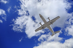 Aircraft flying in blue cloudy sky Royalty Free Stock Photography