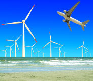 Aircraft is flying in eco power of wind turbines in the sea skyl Royalty Free Stock Photos