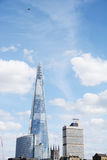 Aircraft flying high above The Shard in London, England Royalty Free Stock Images