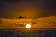 Aircraft flying over amazing tropical ocean at sunrise. Dominican Republic travel destinations. Airplane flying over amazing tropical ocean at sunset. Punta Royalty Free Stock Image
