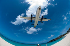 Aircraft flying over beach. Fish eye view of aircraft flying over Maho beach with blue sky and cloudscape background, Saint Martin, Caribbean Royalty Free Stock Photos