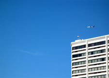 Aircraft flying over hotel stock photography