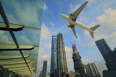 Aircraft flying over the modern city buildings over Stock Photos