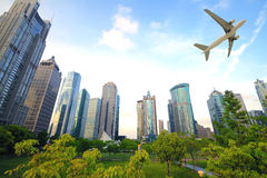 Aircraft flying over the modern city buildings over Stock Photo
