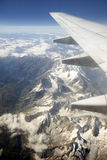 Aircraft flying over mountains. Wing over aerial flying over snow capped mountain range Stock Photo
