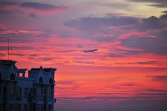 Aircraft flying in red sunset Stock Photo