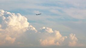 Aircraft flying through the sky with giant clouds at sunset