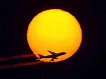 Aircraft flying through the sun Stock Photos