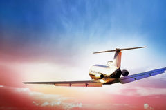 Aircraft flying into sunset Stock Image