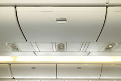Aircraft interior. Commercial aircraft interior in airplane cabin, Overhead compartment Stock Photos