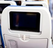 Aircraft interior with seats and blank touch screens displays. stock images