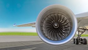 Aircraft jet engine close-up, airplane wing and chassis of landing gear wheel parked at the airport on a sky background, panorama. Aircraft jet engine close-up Stock Photo
