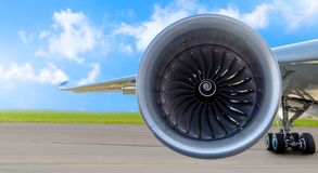 Aircraft jet engine close-up, airplane wing and chassis of landing gear wheel parked at the airport on a sky clouds background, pa. Norama royalty free stock photo