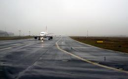 Aircraft landing on foggy runway Royalty Free Stock Photos