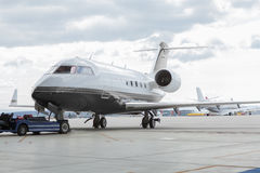 Aircraft learjet Plane in front of the Airport with cloudy sky. And sun Stock Photo