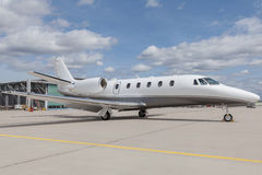 Aircraft learjet Plane in front of the Airport with cloudy sky. And sun Royalty Free Stock Images