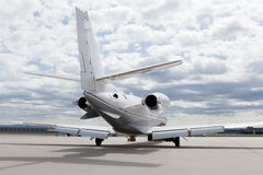 Aircraft learjet Plane in front of the Airport with cloudy sky Stock Photo