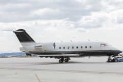 Aircraft learjet Plane in front of the Airport with cloudy sky. And sun Royalty Free Stock Image