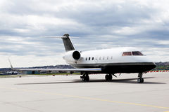 Aircraft learjet Plane in front of the Airport with cloudy sky. And sun Royalty Free Stock Photo