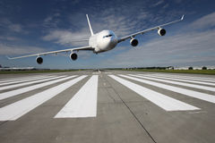 Aircraft low pass. White airplane overflights low over the runway threshold Stock Image