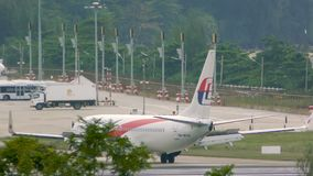 Aircraft of Malaysia Airlines turn from runway to taxiway. PHUKET, THAILAND - NOVEMBER 28, 2016: Rear view of Malaysia Airlines airplane turns from runway to stock video