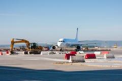 Aircraft maneuvering in the airport. Aircraft maneuvering between excavators and bulldozers royalty free stock photos