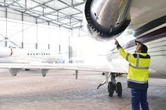 Aircraft mechanic/ ground crew  inspects and checks the turbine. Of a jet in a hangar at the airport Royalty Free Stock Photo