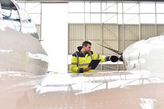 Aircraft mechanic inspects and checks the technology of a jet in. A hangar at the airport Royalty Free Stock Image