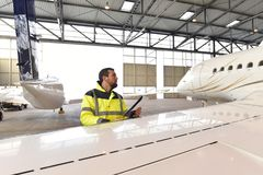 Aircraft mechanic inspects and checks the technology of a jet in. A hangar at the airport Royalty Free Stock Photos