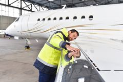 Aircraft mechanic inspects and checks the technology of a jet in. A hangar at the airport stock photos