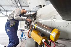 Aircraft mechanic repairs an aircraft engine in an airport hanga. R Royalty Free Stock Images