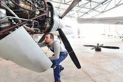 Aircraft mechanic repairs an aircraft engine in an airport hanga Stock Image
