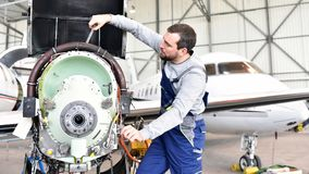 Aircraft mechanic repairs an aircraft engine in an airport hanga. R Royalty Free Stock Photos
