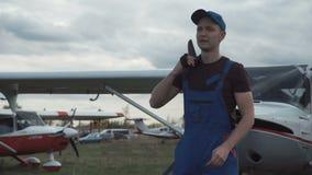 Aircraft mechanic looking at sky. Aircraft mechanic standing at ground and looking at sky stock footage
