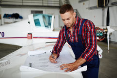 Aircraft Mechanic Working with Plans Stock Images